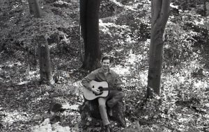 Jon in the forest with old guitar